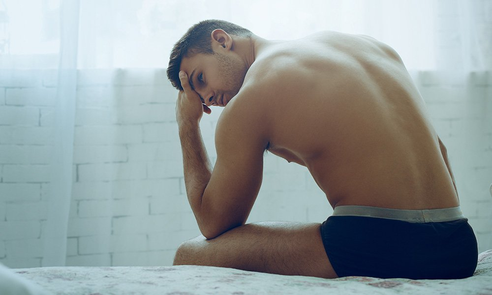 Muscular young man sitting on a bed in his underwear.
