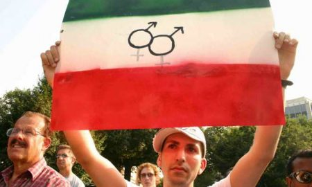 A photo of a man holding up an Iranian flag and equal rights logos.