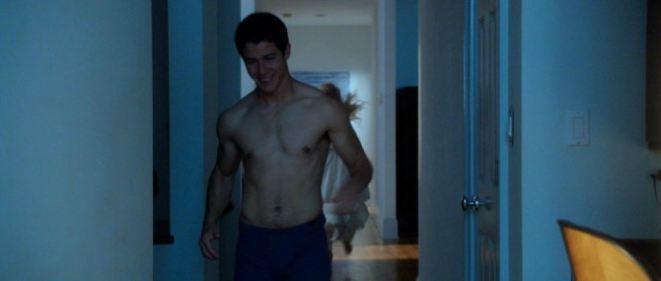A photo of Nick Jonas walking shirtless.