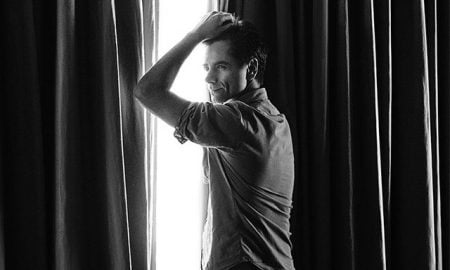 This is a photo of John Stamos posing for 'Paper Magazine'.