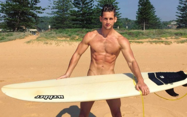 This is a photo of model Max Emerson about to go surfing.