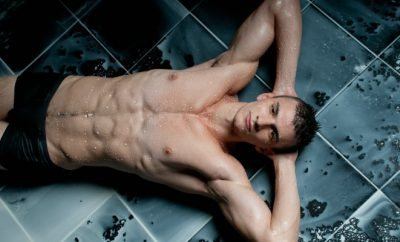 Hot guy laying on floor covered in milk.