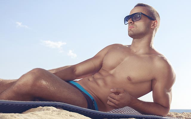 This is a photo of a single gay man laying on the beach.