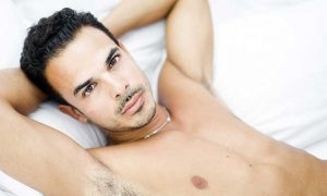 A good looking Hispanic man laying in a bed.