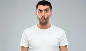 Man with funny fish-face over gray background.