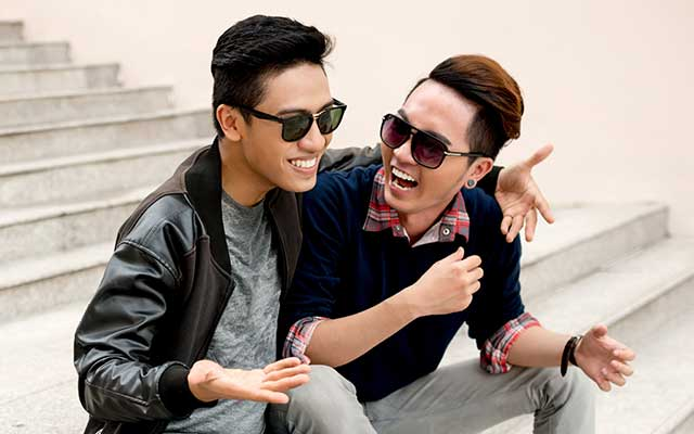 Two Asian men sitting on steps and laughing.