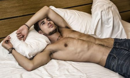 This is a photo of a good looking young man laying on a bed.