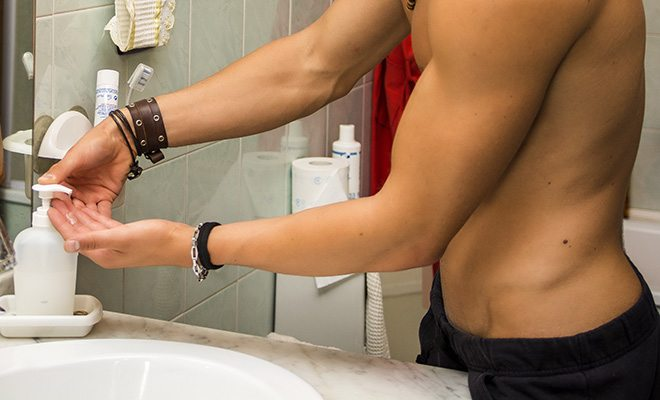 Young man pumping soap into hand