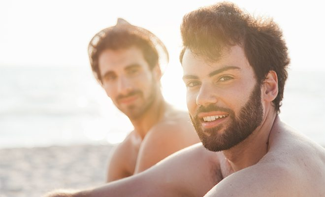 Gay men sitting on the beach
