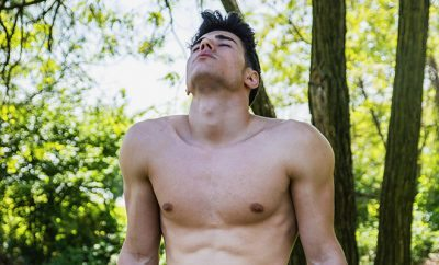 Shirtless handsome young man resting in city park, sitting on wood bench