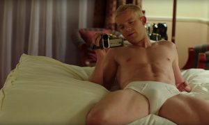 Russell Tovey laying on a bed in his underwear