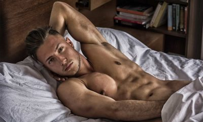 A shirtless young man in bed