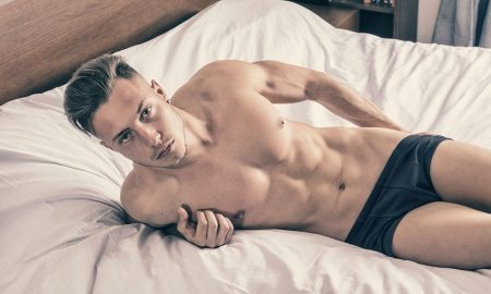 Guy laying on bed in underwear