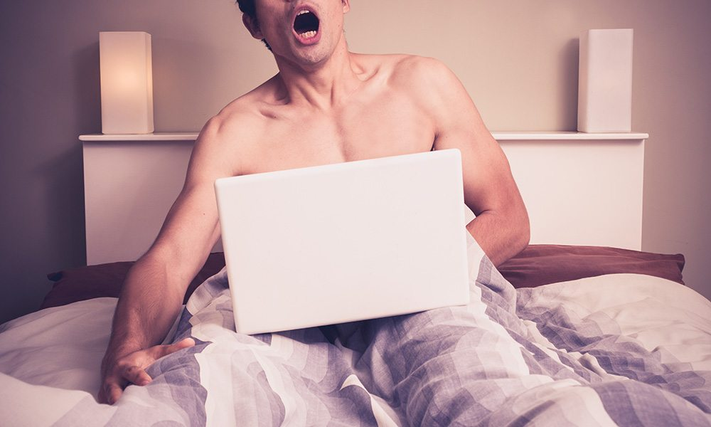 Man using a computer and masturbating in bed