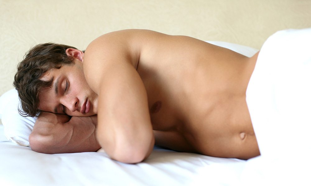 Sexy man asleep in bed.