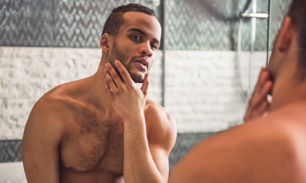 Shirtless man with beard looking in the mirror