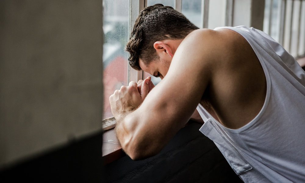 Muscular man leaning on window