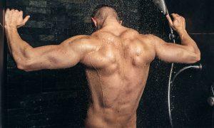 Muscular man taking a shower