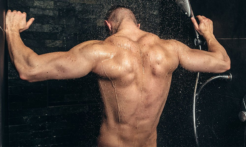 Muscular man taking a shower