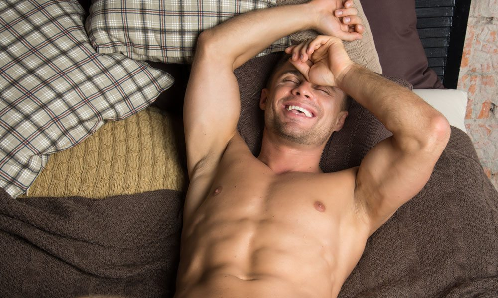 Athletic guy is lying on the bed.