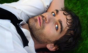 Man with blue eyes laying in the grass