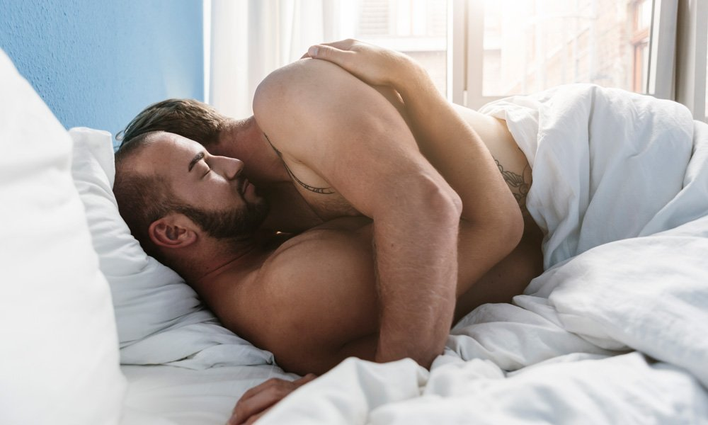 Gay couple hugging in bed.