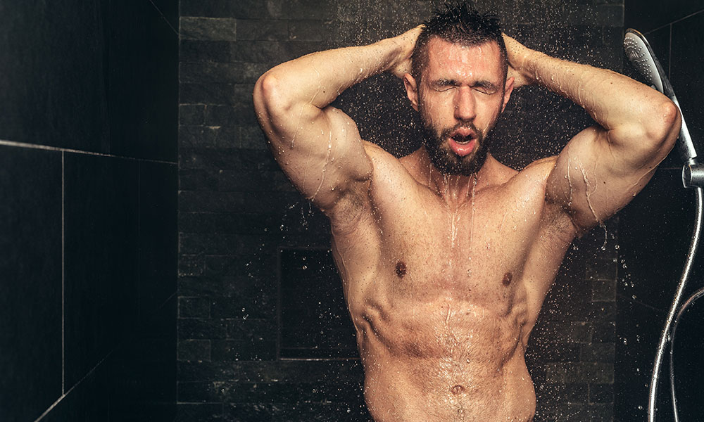 Attractive muscular man taking a shower, details of man in rainshower.