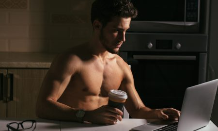 A shirtless young man working on a computer