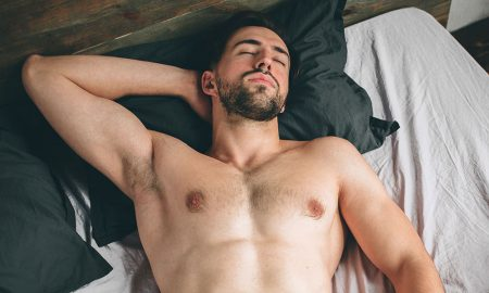Portrait of a fit male model asleep in luxurious bedroom