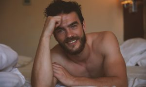 Man laying on bed smiling