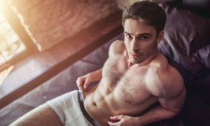 Man moisturize in underwear in bed