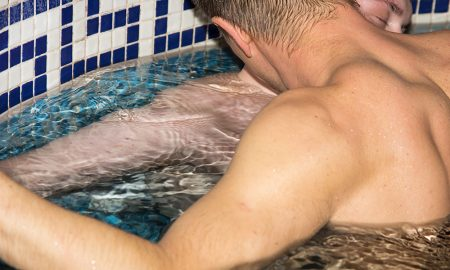 Two men kissing in a pool