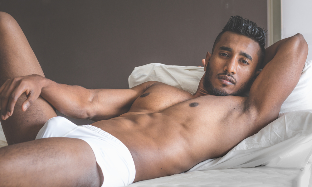 Man in his underwear laying on bed