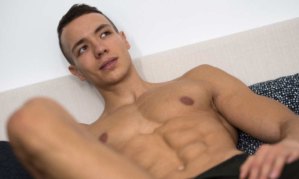 Young guy laying shirtless on a bed