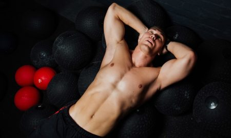 Portrait of a muscular man resting and lying on the floor in fitness gym