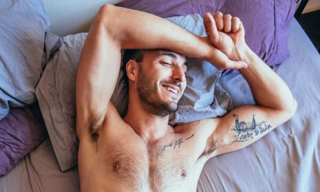 Man in bed laughing