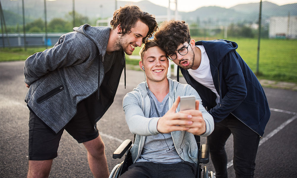 A boy in wheelchair with smartphone and teenager friends taking selfie on a playing field.
