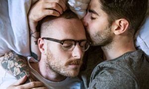Gay couple lying on bed at home