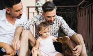 Gay couple with daughter and dog on balcony using digital tablet