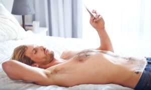 Gay man laying on the bed using Grindr