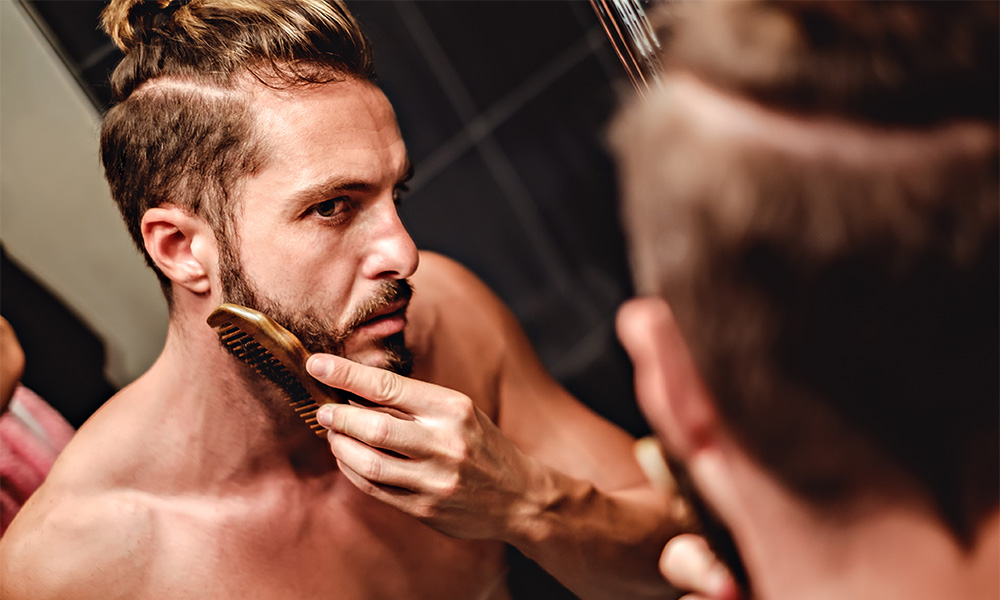Hipster man focusing on combing beard in front of a mirror