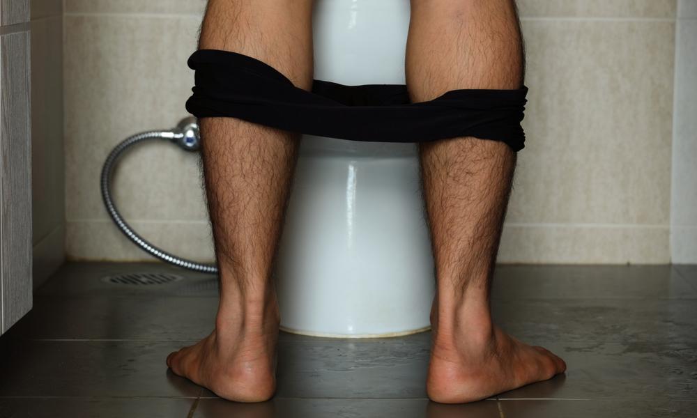 Man standing at a urinal.