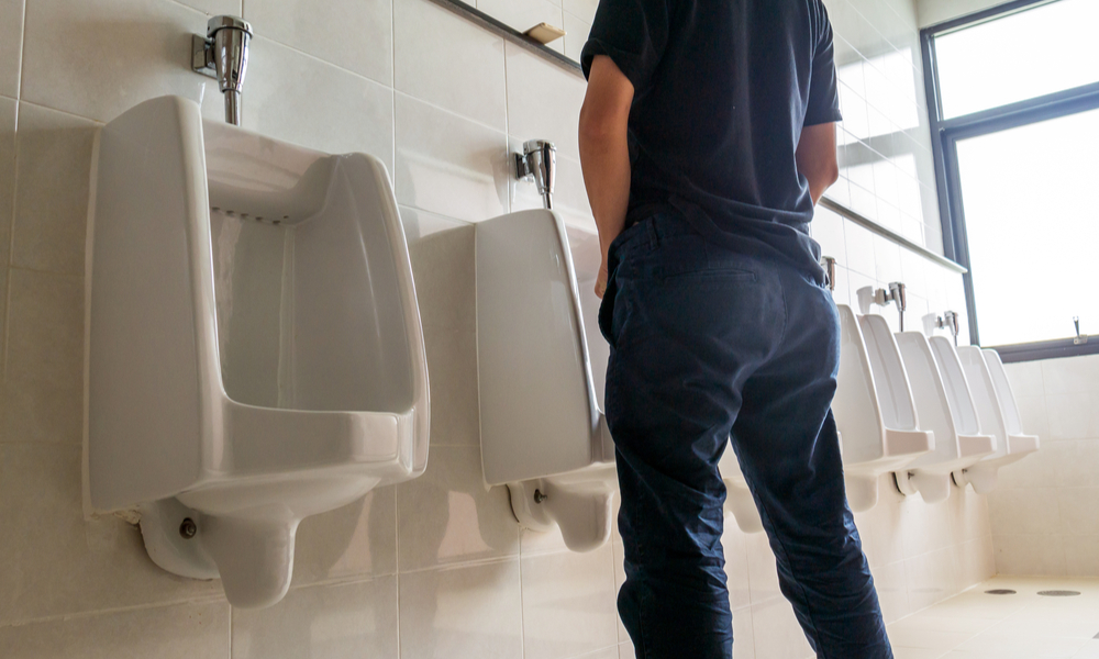 Man standing at a urinal.