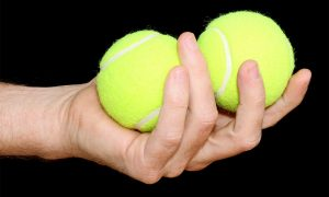 Man holding two tennis balls in one hand