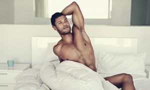 Shot of a handsome naked man in bed in the morning