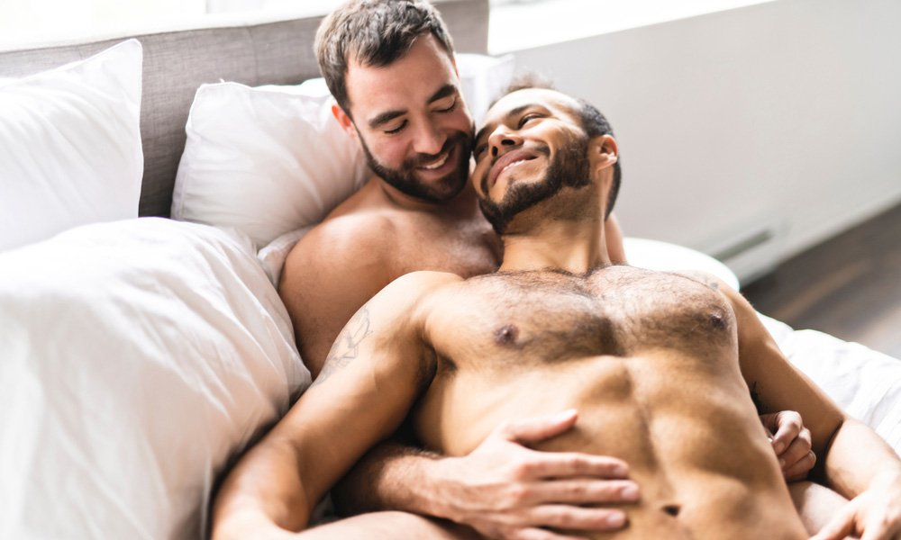 This is a photo of two men cuddling in bed.