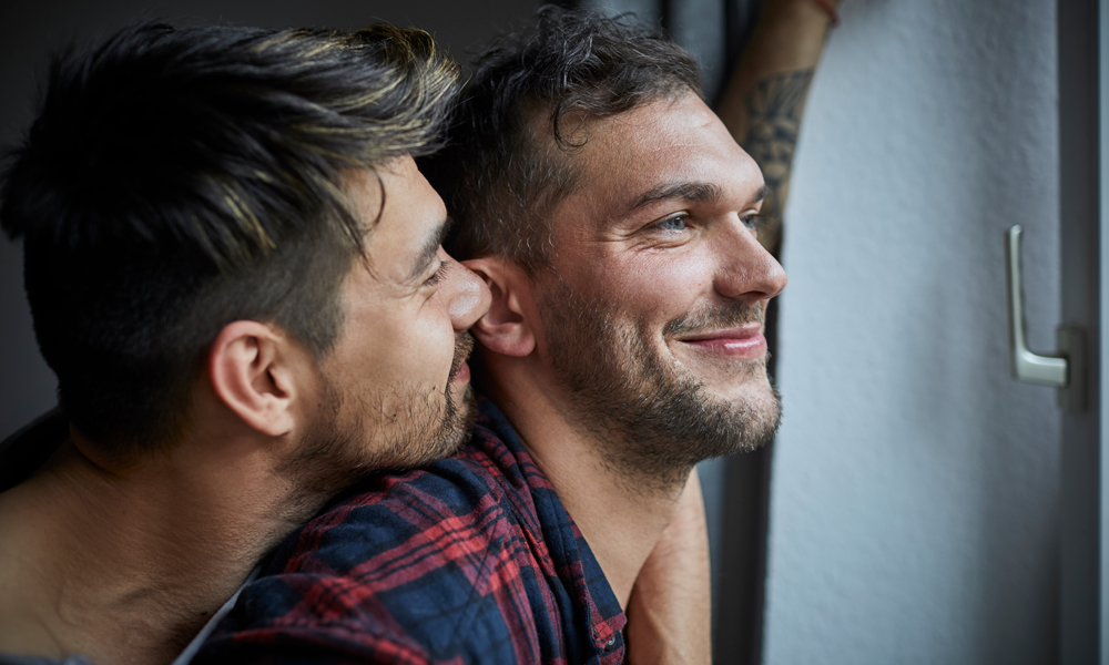 Gay man embracing boyfriend at the window