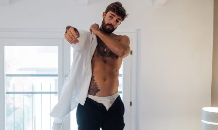 Adult man with tattoos putting on shirt in bedroom