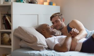 Gay couple lying in bed together, hugging