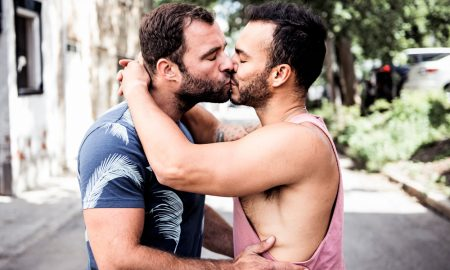 A gay couple kissing in public